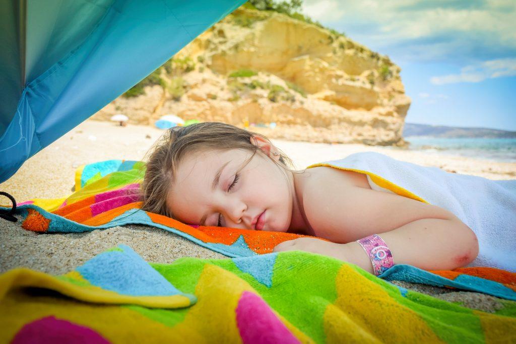 Natürlich ist das Toben am Strand anstrengend. Unterm Sonnenschirm ist dann ein guter Platz für ein Nickerchen.